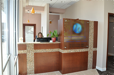 Clear, bright photo of front desk, showing the front desk staff