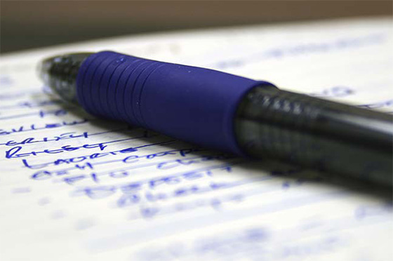Blue pen and pad with written list