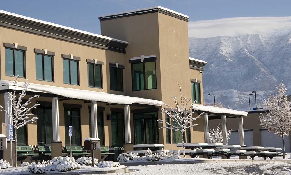 Snow covered business building near mountains in the background