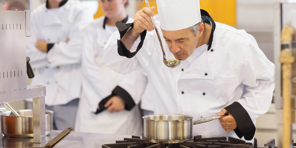 Professional chef tasting soup from a ladle