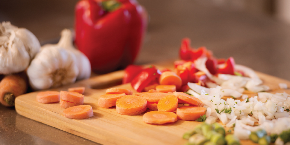 Sliced ingredients for soup sitting on cutting board
