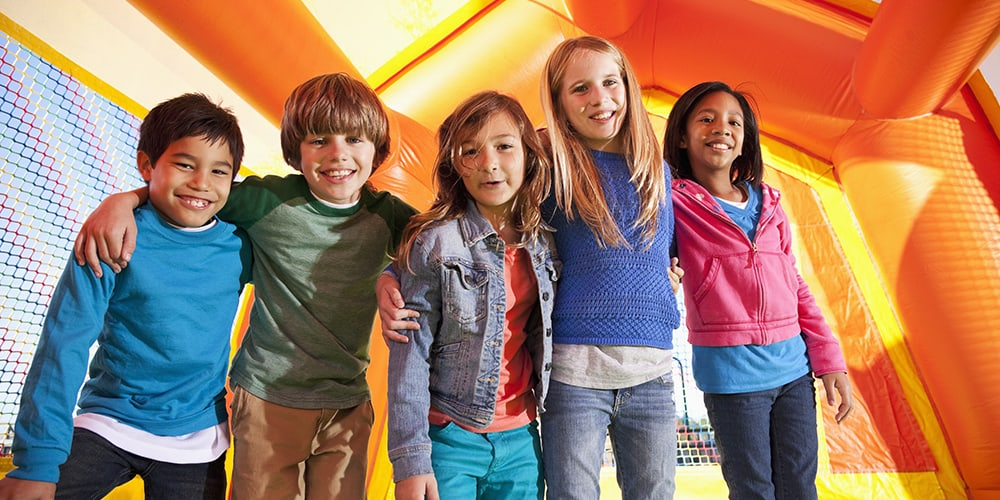 Diverse group of children playing in a bouncy house