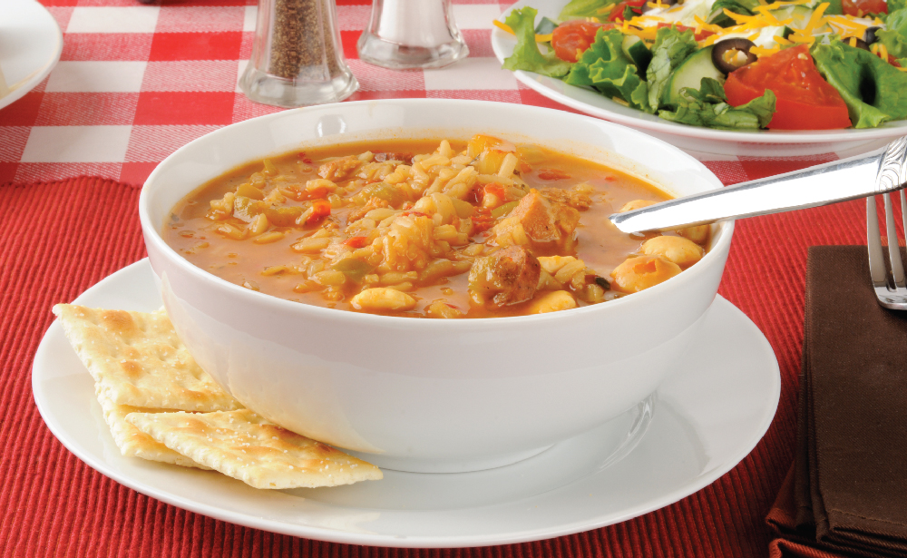 Bowl of soup with crackers and a side salad