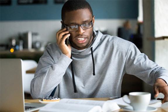 Man in gray hoodie on the phone