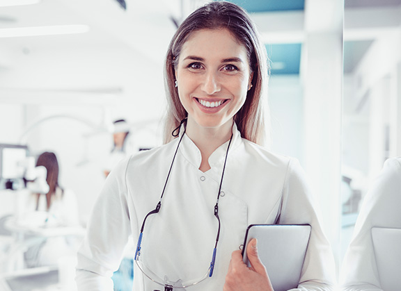 Doctor smiling holding clipboard