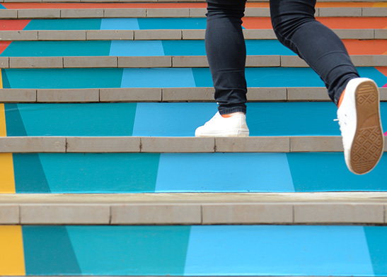 person walking up colorful stairs