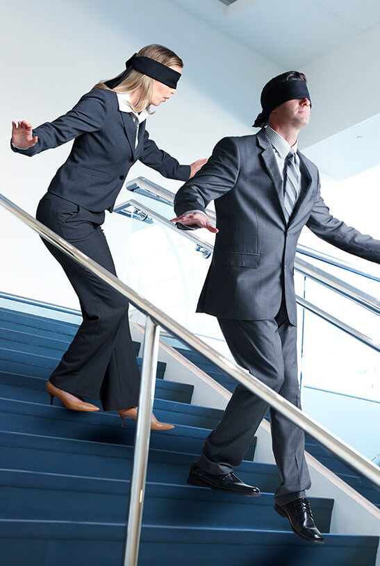 pair of business people walking down stairs blindfolded