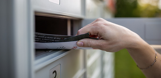 Hand pulling out mail from mail box