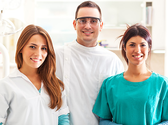 Doctor and hygienists smiling