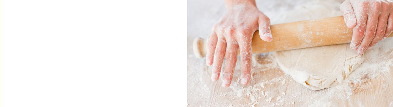 Hands rolling bread dough