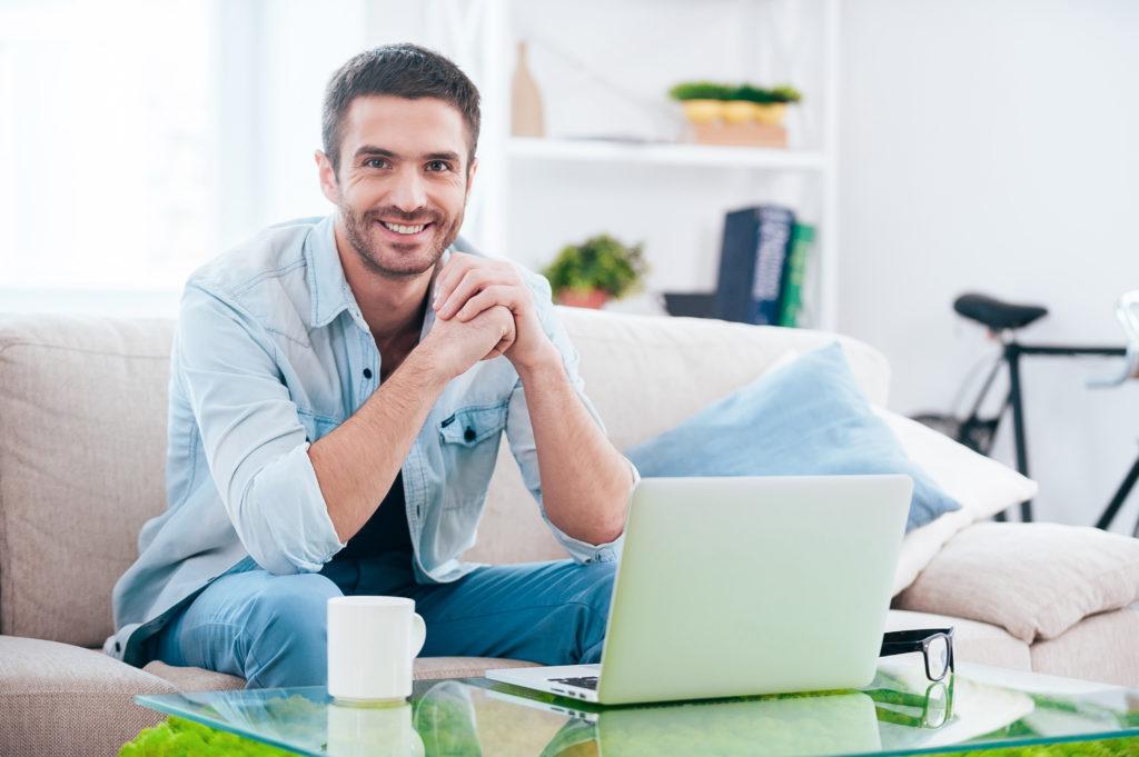 Man sitting next to laptop