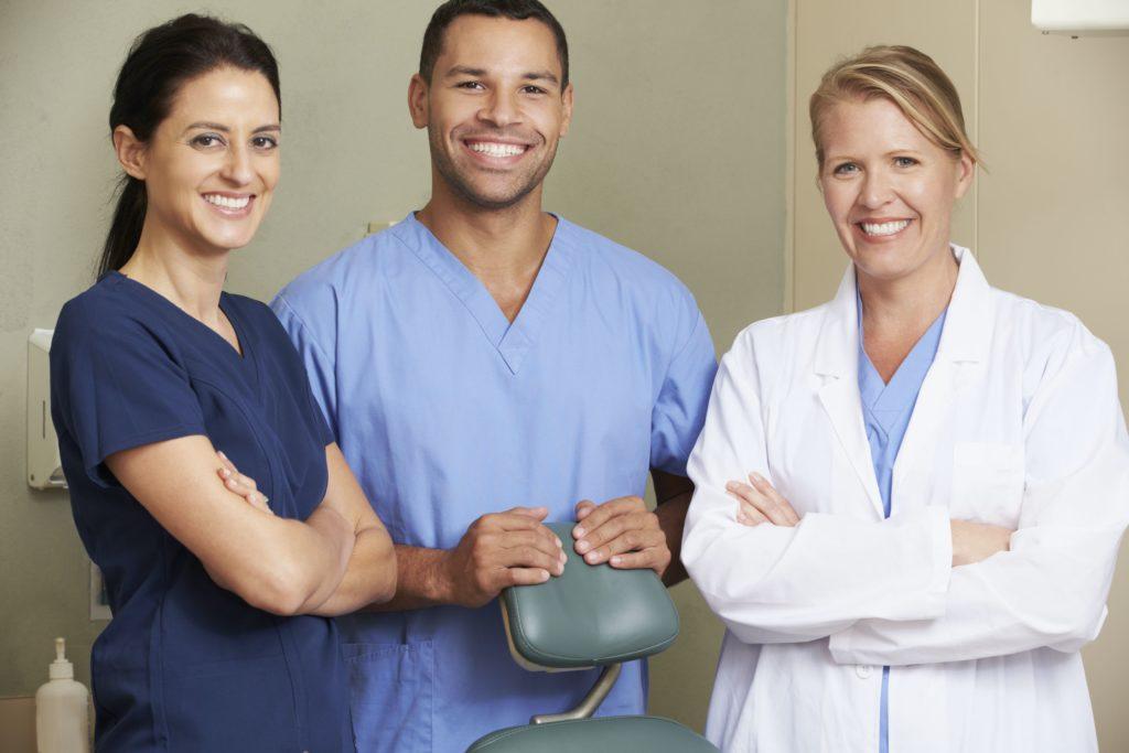 3 dentists standing around dental chair