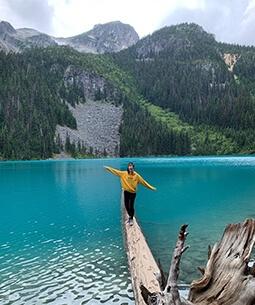 Chloë balancing on a log in a lake